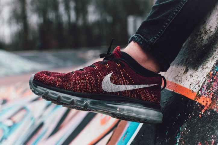 close up photography of red and black nike running shoe