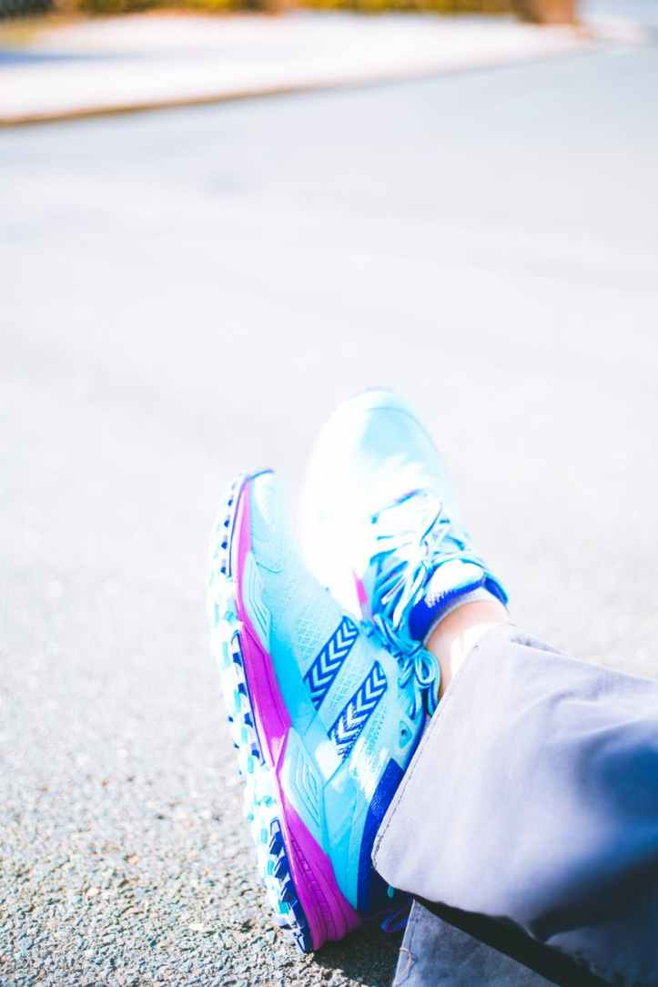 person wearing pair of blue and pink running shoes